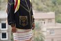 أحد سكان قرية رجال ألمع يرتدي الزي التقليدي وتاج من الزهور على رأسه